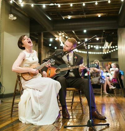 Couple playing Music together at wedding, dress by Janay A