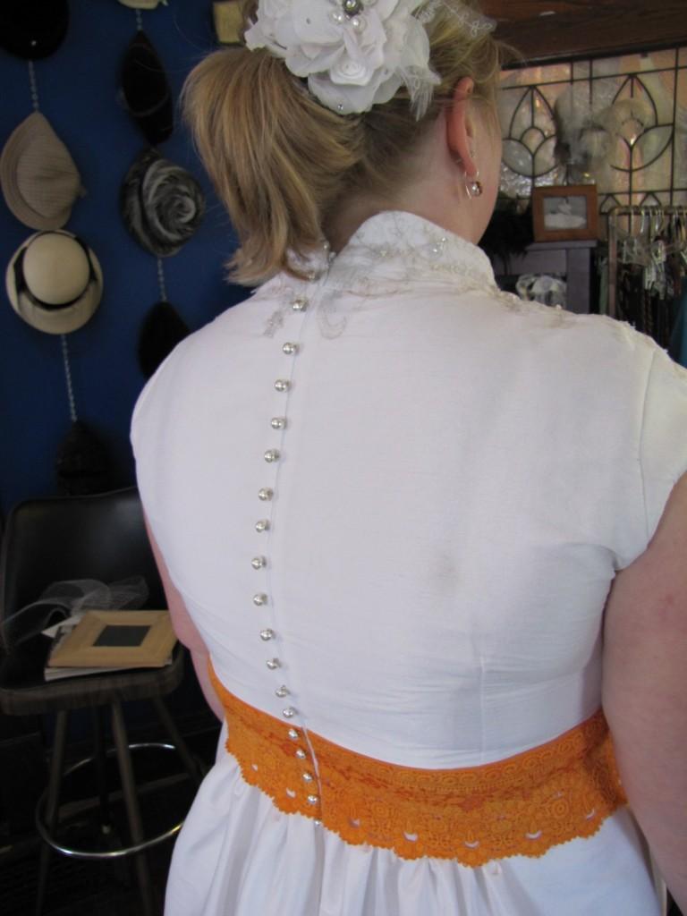 Fun burnt orange sash & pearl button adornments.